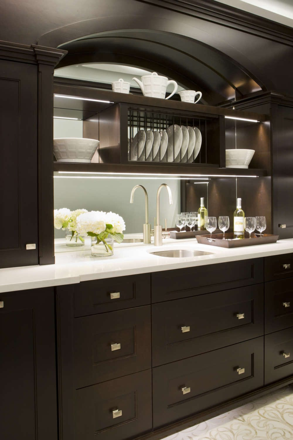 Butler's pantry features shaker style, frameless fully custom Rutt Handcrafted Cabinetry in walnut with a dark stain, beautiful moldings and mirror inserts. Design by Tom Vecchio of Bilotta Kitchens.