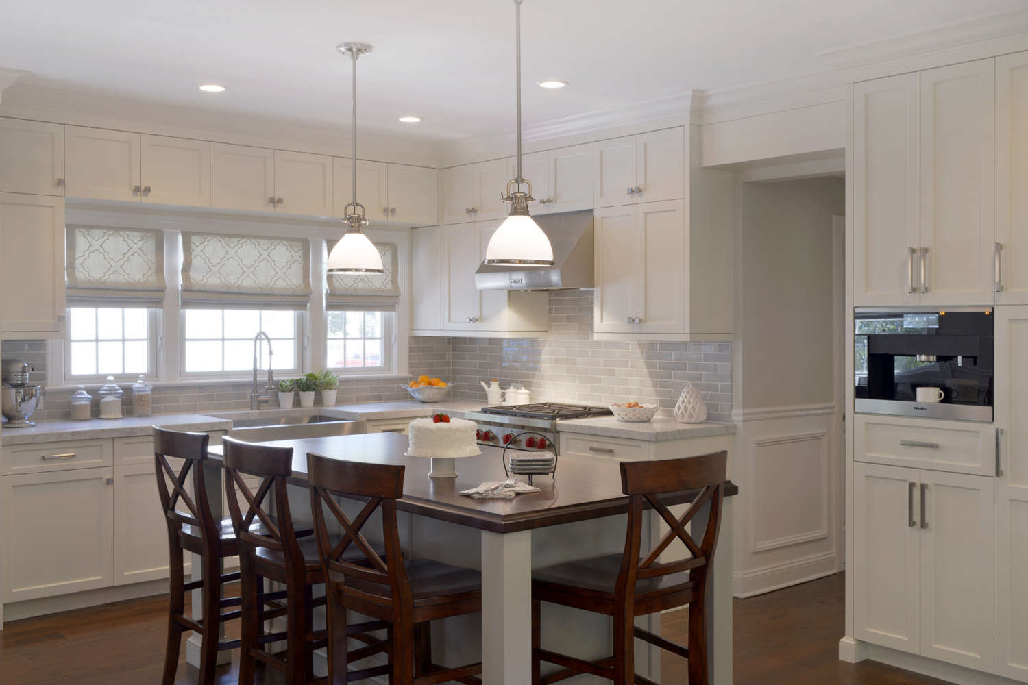 L-shaped transitional kitchen features island with seating and fully custom, double-tiered white painted shaker style Bilotta Cabinetry. Dove gray subway tiles and monochromatic fabric roman shades bring warmth to the room. Design by Jeni Spaeth of Bilotta Kitchens.