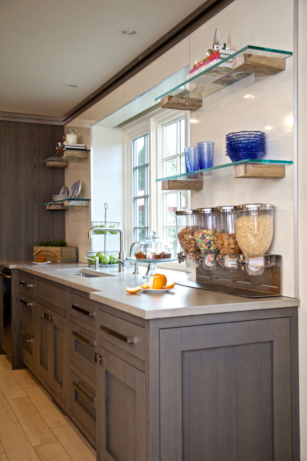 Family-friendly kitchen features porcelain plank style tile flooring, light quartz countertops, shaker style rift white ash stained jully custom cabinets by Bilotta and open glass shelving. Design by Jeff Eakley of Bilotta Kitchens.