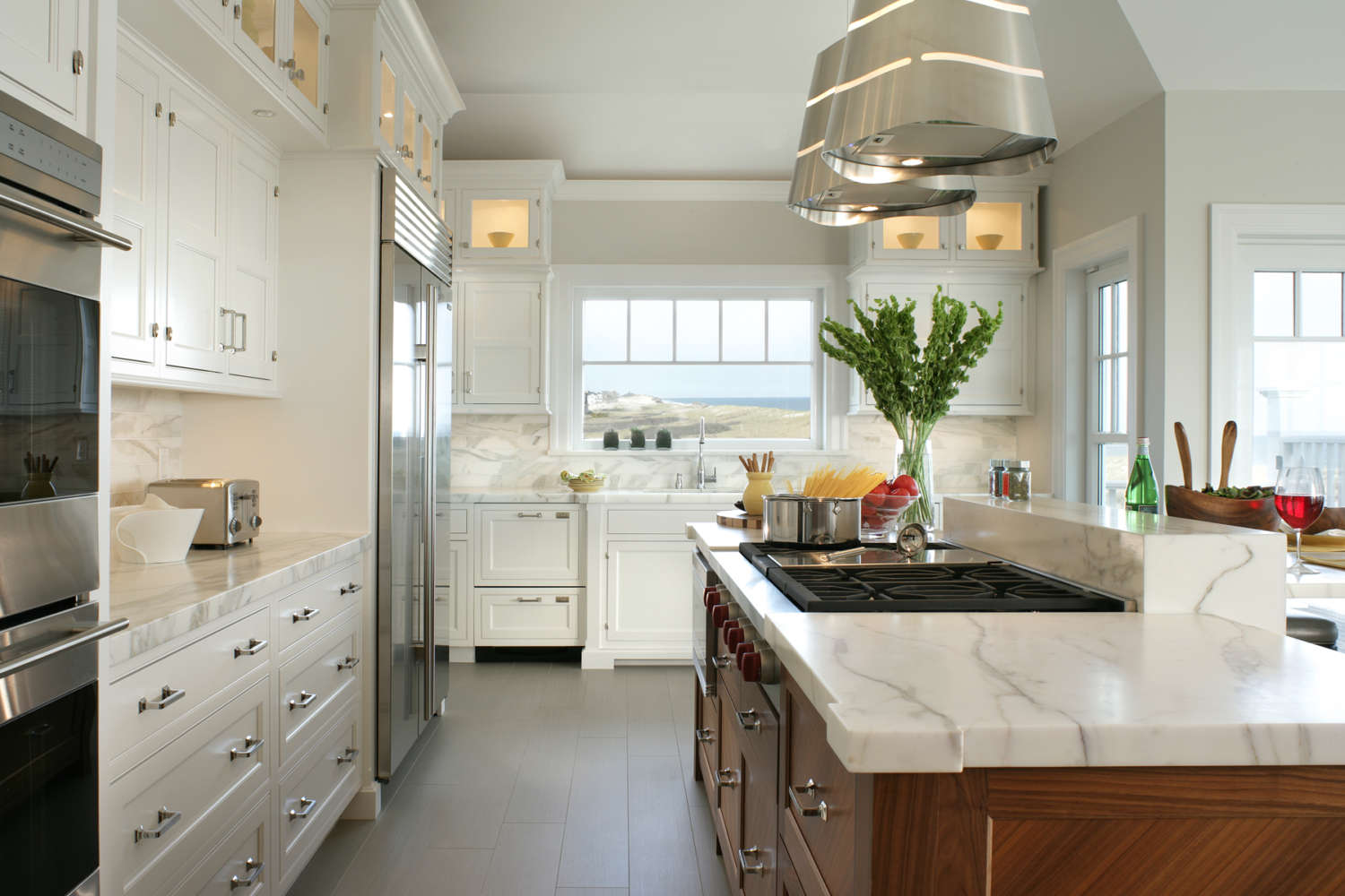 Hamptons kitchen features fully custom white-painted shaker-style, double tiered Bilotta Cabinetry with lit glass-front cabinets on top. The kitchen also incorporates fully custom natural walnut Bilotta cabinetry, white marble countertops and backsplash, and light grey porcelain floor tiles. Design by Daniel Popescu of Bilotta Kitchens.