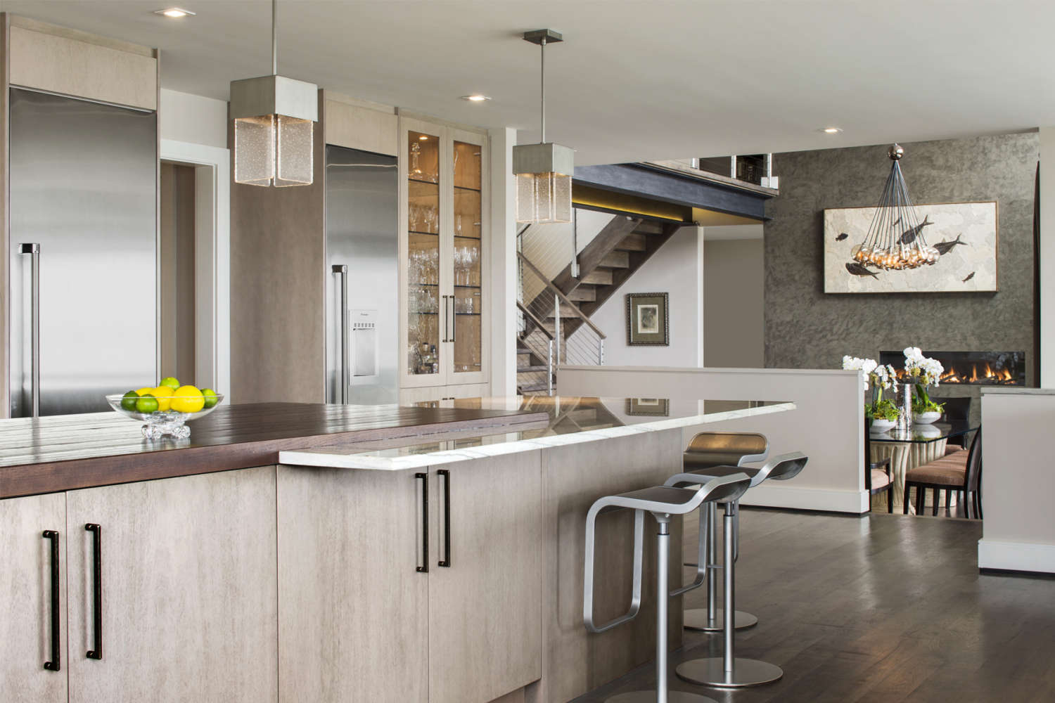 Transitional kitchen with flat panel, framelss, fully custom Bilotta Cabinetry in mahogany opens up into adjacent sunken livingroom. Open staircase features airplane wire. Kitchen island has seating and polished marble countertop. Design by Randy O'Kane, CKD, of Bilotta Kitchens.