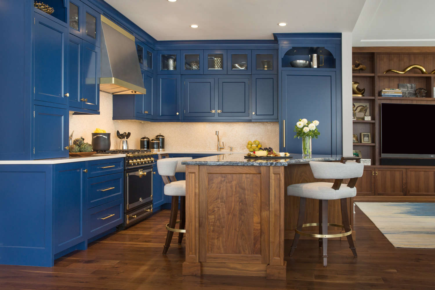 L-shaped kitchen with blue painted custom kitchen cabinets with shaker style doors. Walnut island with seating. Bilotta custom cabinets and shelving in walnut with mid-century modern vibe in adjacent living room area. Designed by Jeni Spaeth of Bilotta Kitchens.