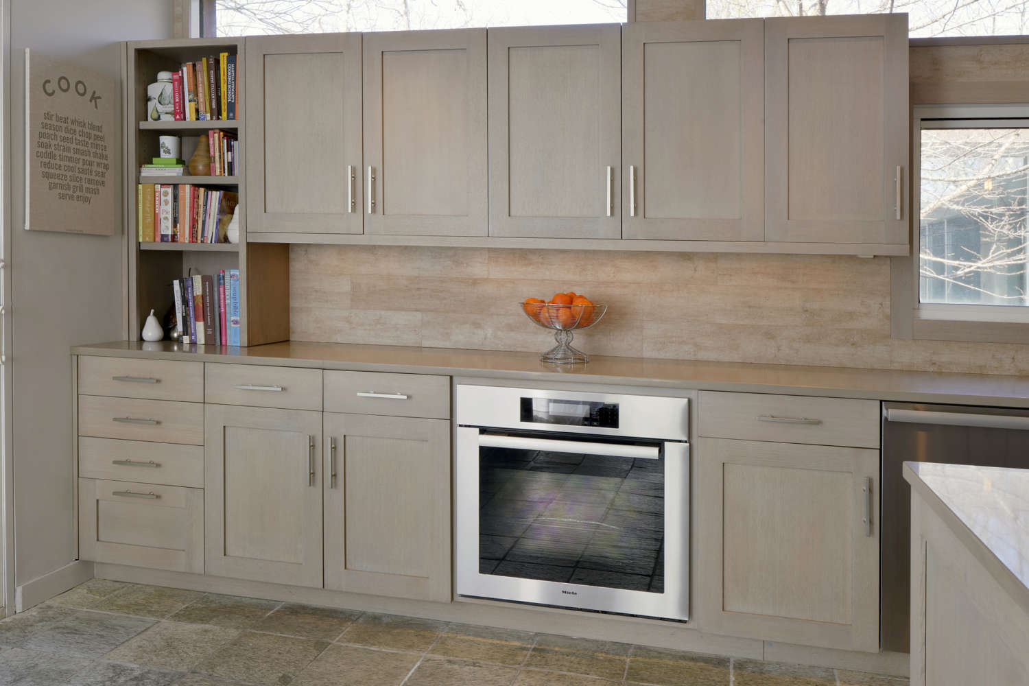 Rustic kitchen features fully custom frameless, shaker style Bilotta Cabinetry in rift cut white oak with Driftwood stain, neutral quartz counter and soft travertine backsplash with complementary floor tile. Design by Danielle Florie of Bilotta Kitchens.