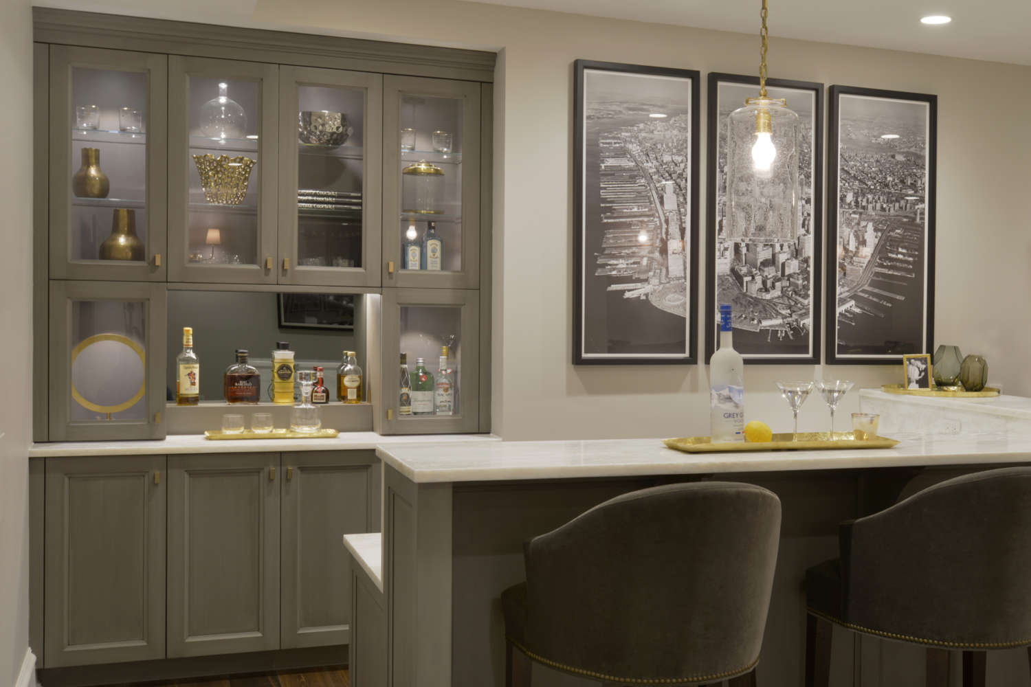 Classic styled bar area features custom sage green painted frameless Bilotta Cabinetry with glass front doors and gold hardware, white marble countertop and seating illuminated with a simple gold chain pendant light. Design by Tom Vecchio of Bilotta Kitchens.