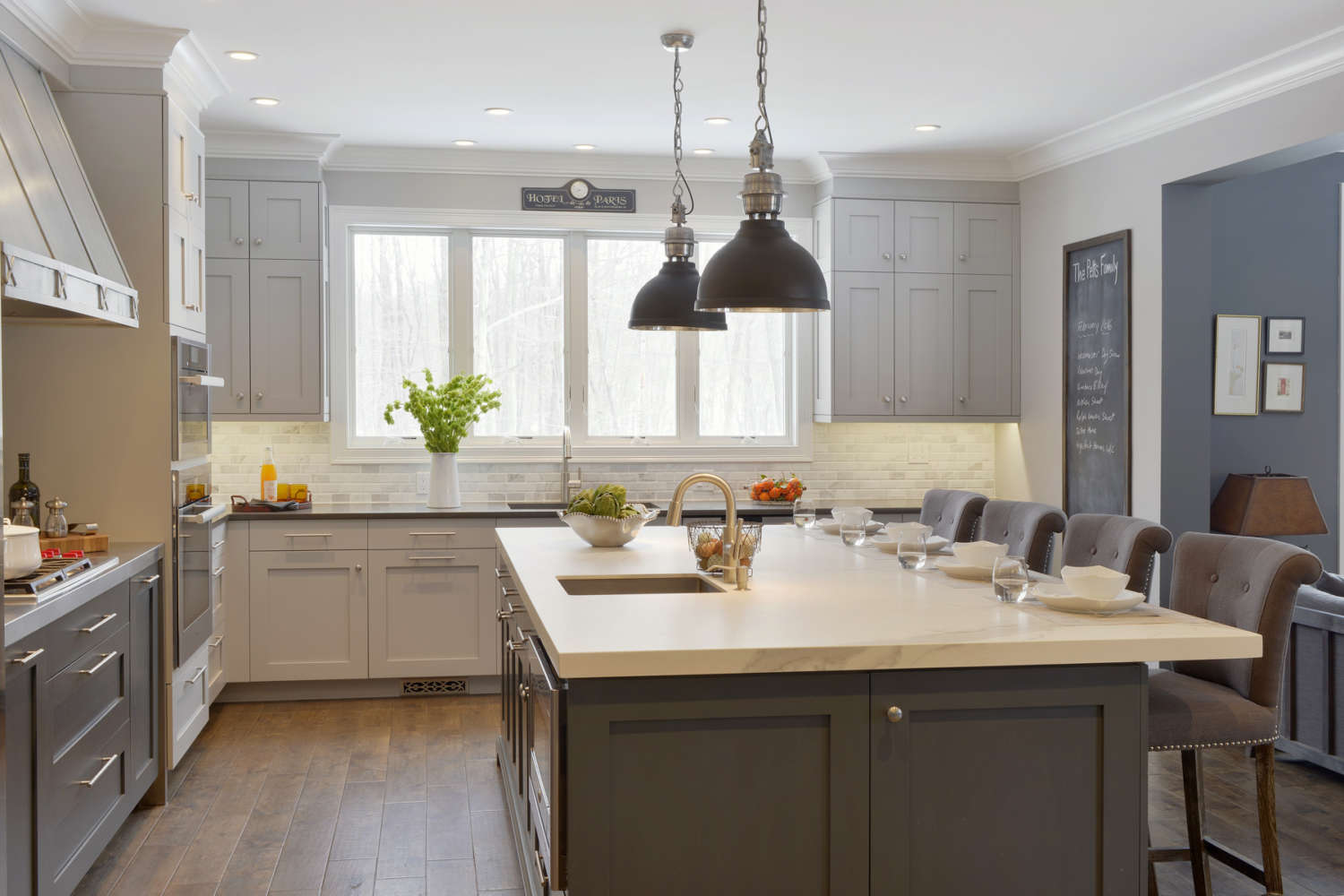 Expansive kitchen and living space features an island with fully custom, frameless shaker style dark grey painted Bilotta Cabinetry and light quartz countertop. The island is lit with two dark dray industrial dendant lights. Design by Paulette Gambacorta of Bilotta Kitchens.