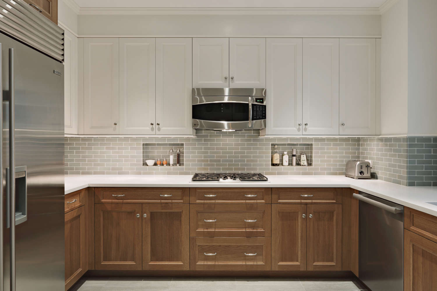 U-shaped kitchen features fully custom, frameless, shaker style Rutt Handcrafted Cabinetry in a mix of rift cut white oak and white painted finish, white quartz counters, neutral-toned subway tile backsplash and brushed stainless accents. Design by Tom Vecchio of Bilotta Kitchens.