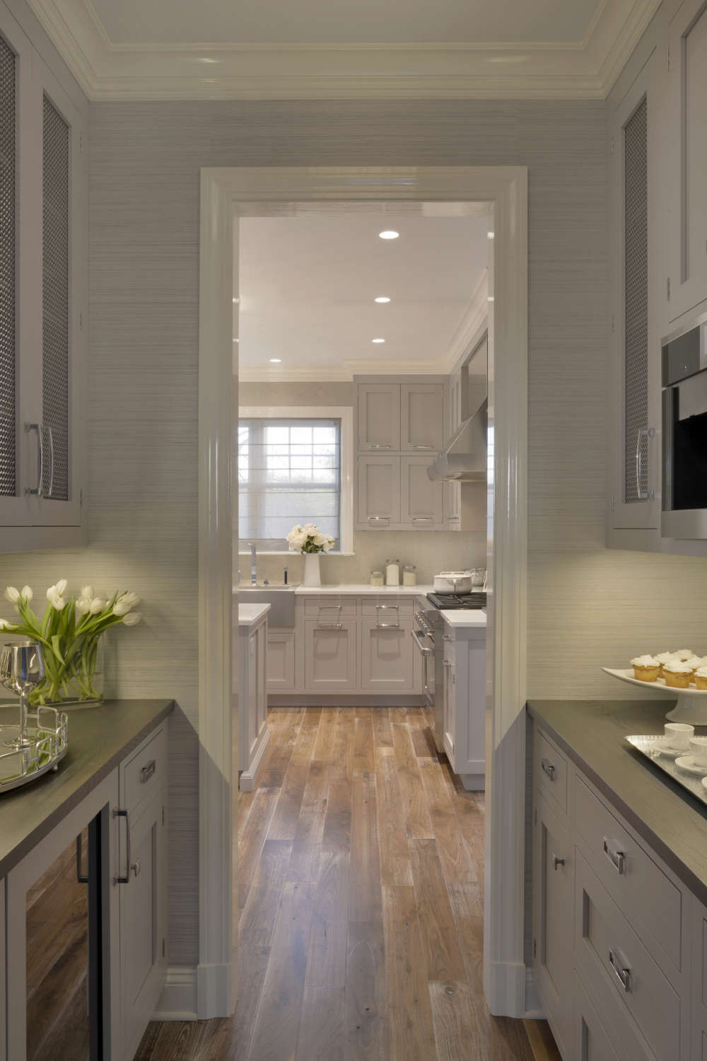 Butler's pantry features light grey painted shaker style Biotta cabinetry with metal door inserts, grey walls and espresso countertops. Pantry opens into an expansive kitchen. Design by Randy O'Kane, CKD, of Bilotta kitchens.