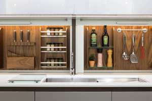 Kitchen accessories organized on a walnut backsplash above a white quartz countertop.