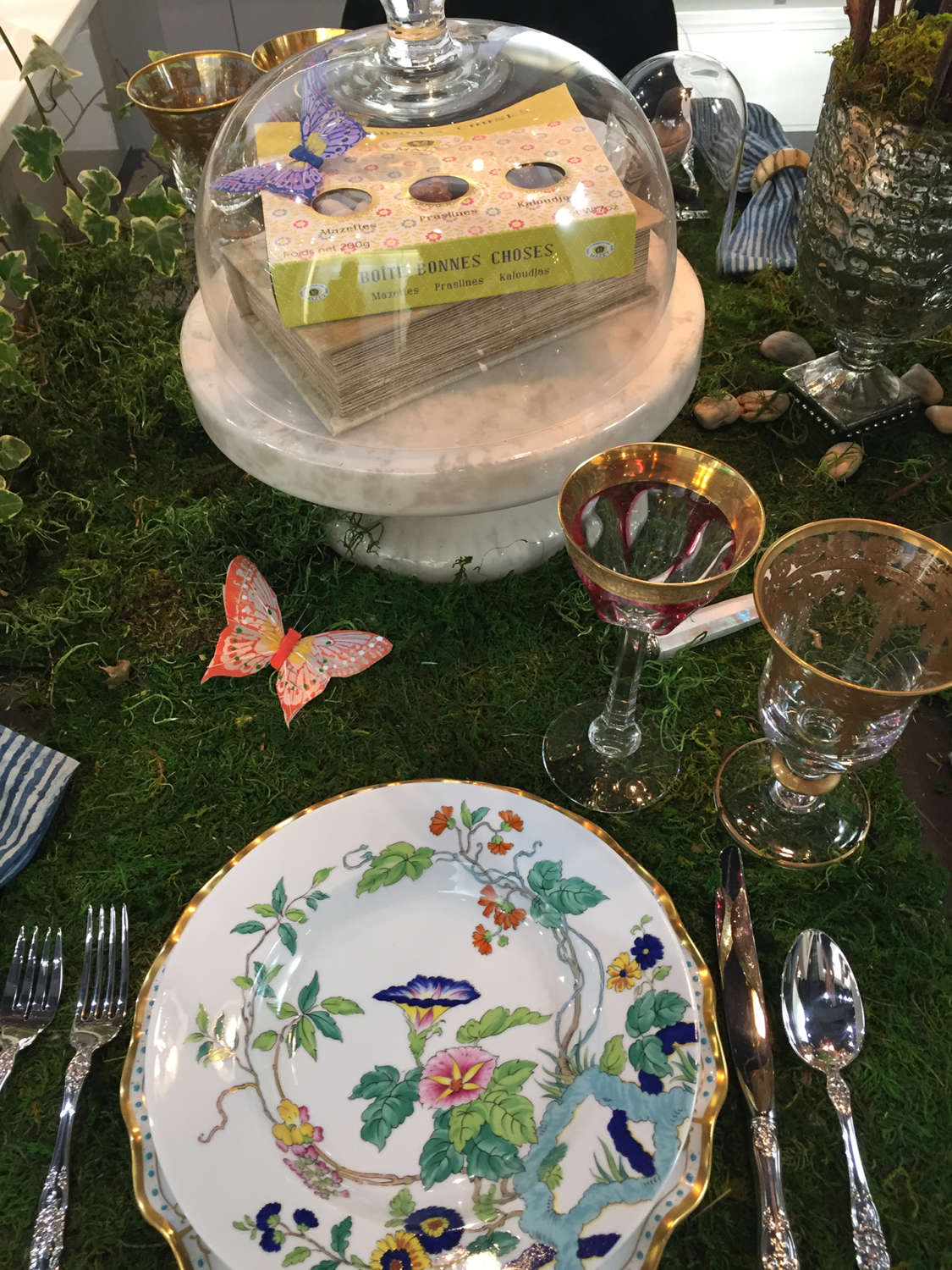 An Art of The Table tablescape set on moss with butterfly accents.