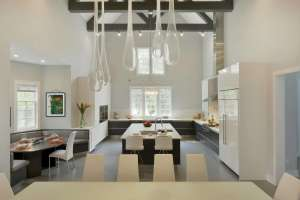Contemporary all white open kitchen with vaulted ceilings and exposed beams features large center island and blown glass teardrop pendant lighting.
