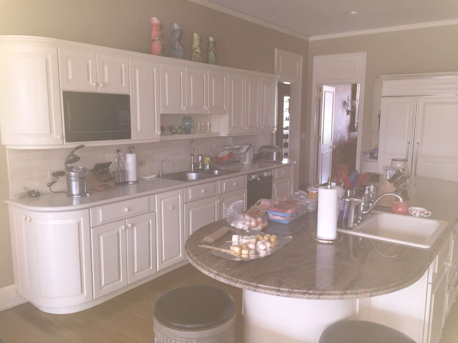 Before picture of dark kitchen with white cabinets and brown granite topped island.