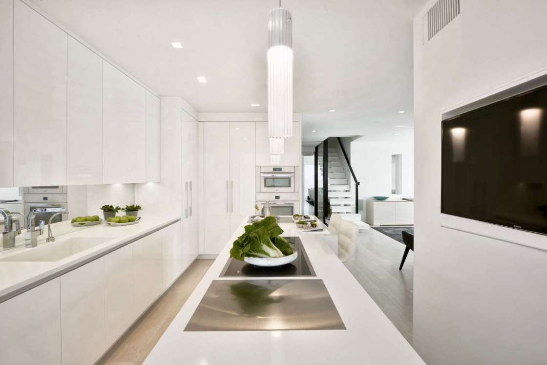 All white contemporary kitchen features a full-length island with cooktop and eating counter, fully custom frameless slab door cabinets by Artcraft, light oak flooring, mirror backsplash and white quartz countertops. Under-counter lighting, dramatic white pendant lights and recessed ceiling lighting further brighten the open space.