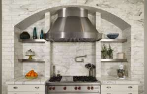 Marble brick hearth designed around stainless hood features arch and built-in stainless shelves. Range is flanked by white-painted custom kitchen cabinets.