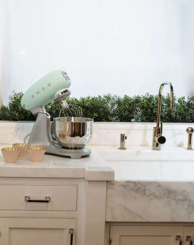 mint-green smeg stand mixer sitting on a marble countertop