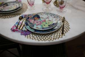 """""""Tobacco Leaf"""" pattern place setting by Mottahedeh with gold flatware on a gold place mat"""