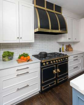 A focal point of this mostly white kitchen is a black and gold La Cornue range with custom hood.