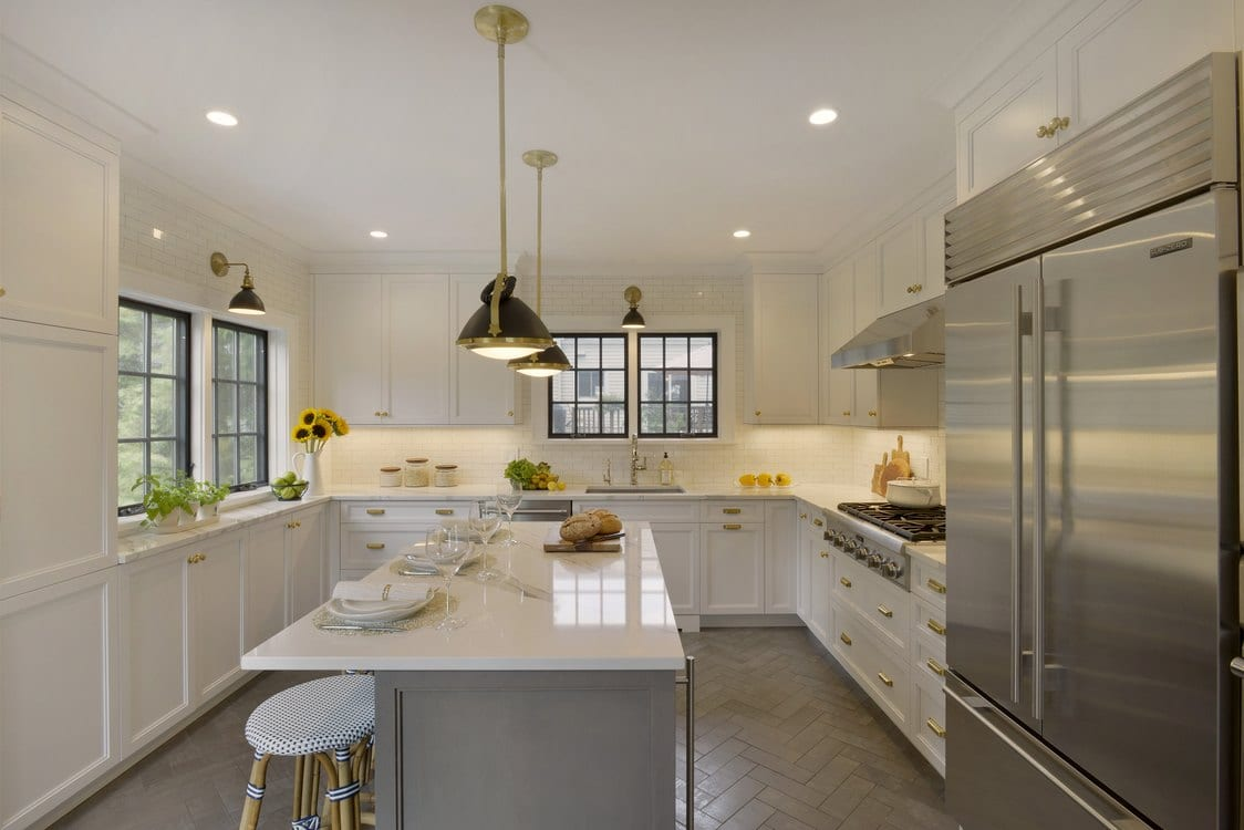 Light-filled transitional kitchen features white painted Bilotta custom cabinetry with brass hardware, glazed ceramic floor tiles set in a herringbone pattern and black and brass pendant lighting.