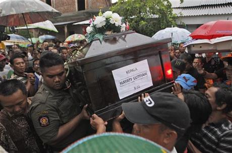 Relatives carry the coffin containing the body of Hayati Lutfiah Hamid, one of the victims of AirAsia Flight 8501, during her burial at a cemetery in Surabaya, East Java, Indonesia, Thursday, Jan. 1, 2015. Hamid became the first victim of the ill-fated AirAsia flight identified and returned to her family Thursday, one of many painful reunions to come, as search crews struggled against wind and heavy rain to find more than 150 people still missing. (AP Photo/Trisnadi)