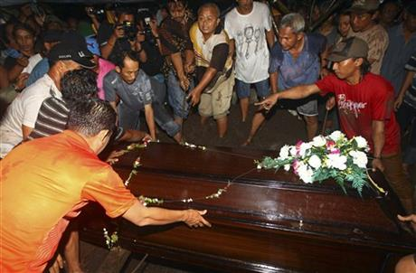 Relatives lower the coffin containing the body of Hayati Lutfiah Hamid, one of the victims of AirAsia Flight 8501, during her burial at a cemetery in Surabaya, East Java, Indonesia, Thursday, Jan. 1, 2015. Hamid became the first victim of the ill-fated AirAsia flight identified and returned to her family Thursday, one of many painful reunions to come, as search crews struggled against wind and heavy rain to find more than 150 people still missing.  (AP Photo/Firdia Lisnawati)