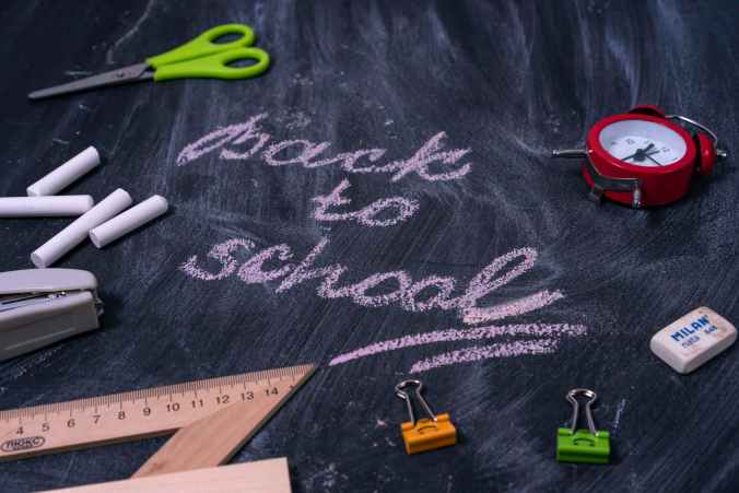 """""""Back to school"""" written on a black backboard"""