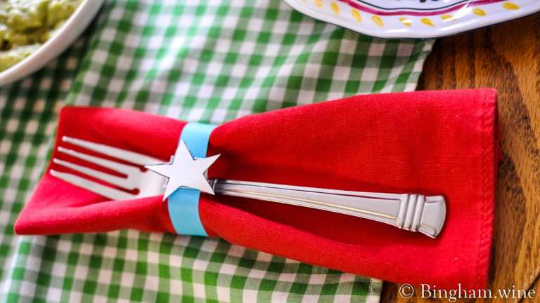 Fork on a red napkin with a paper napkin holder with a white start.