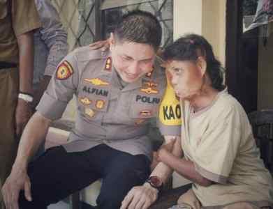 Foto: tanpa risih Kapolres Jember bercengkrama dengan Rohati, seorang ibu dengan cacat fisik.