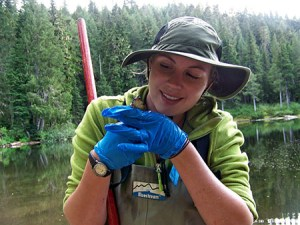 young citizen science woman holding frog with trees and lake background