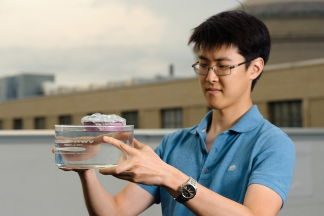 MIT graduate student George Ni holds a bubble-wrapped, sponge-like device that soaks up natural sunlight and heats water to boiling temperatures, generating steam through its pores.