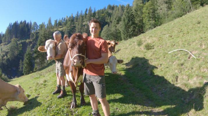 Markus Schaidreiter mit Milchkuh auf der Weide seines Biohofs