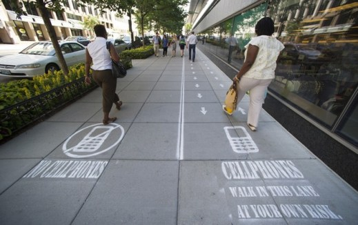 As part of their Mind Over Masses television show, National Geographic divided a one block-long sidewalk into two sections; one for cell phone users and the other for those not using a cell phone in downtown Washington, Thursday, July 17, 2014. The walkway warnings were put there by the brains behind a National Geographic television show as part of a behavioral science experiment. (AP Photo/Cliff Owen)