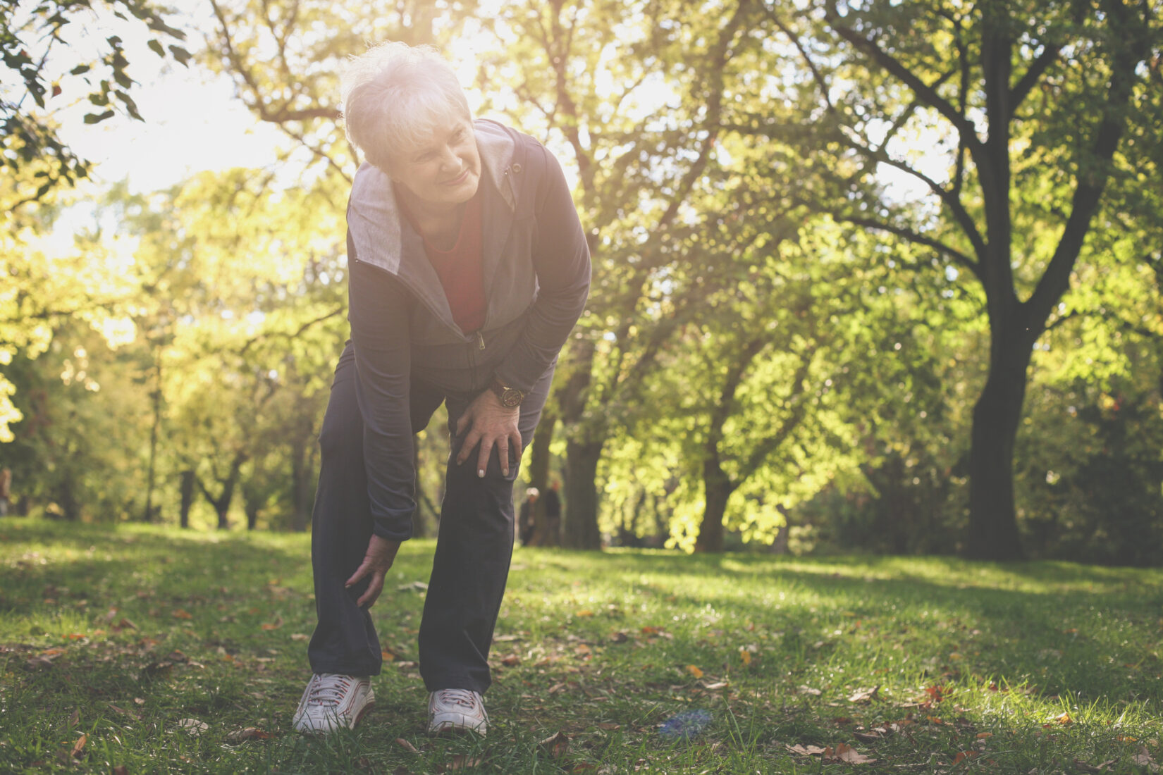 Serious senior woman having pain in leg after exercise.