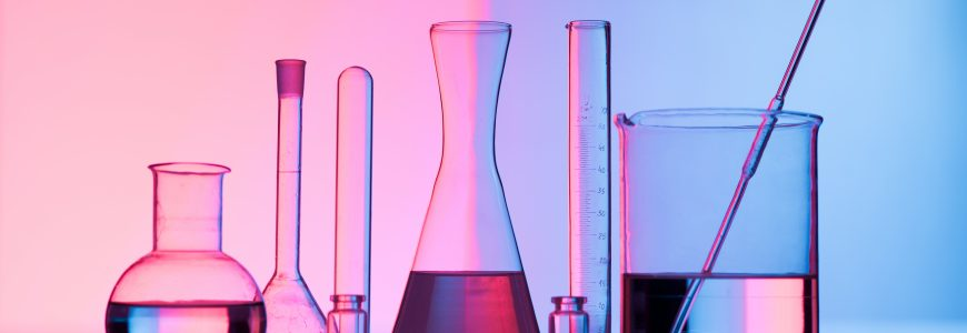 Different laboratory glassware with water and empty with reflection. Pink and blue tint background