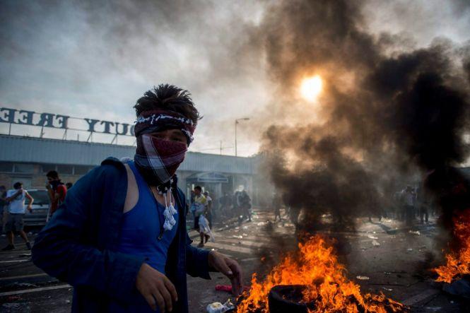 Horgos, 2015. szeptember 16. Tüntető migráns a Horgos-Röszke határátkelőhely szerbiai oldalán 2015. szeptember 16-án. A magyar rendőrök könnygázt és vízágyút is bevetettek a határ magyar oldaláról az őket dobáló illegális bevándorlókkal szemben. MTI Fotó: Sóki Tamás