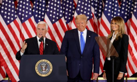 Vice President Mike Pence speaks as U.S. President Donald Trump and First Lady Melania Trump watch on election night in the East Room of the White House shortly after 2 a.m. in Washington, on Nov. 4, 2020. (Chip Somodevilla/Getty Images)