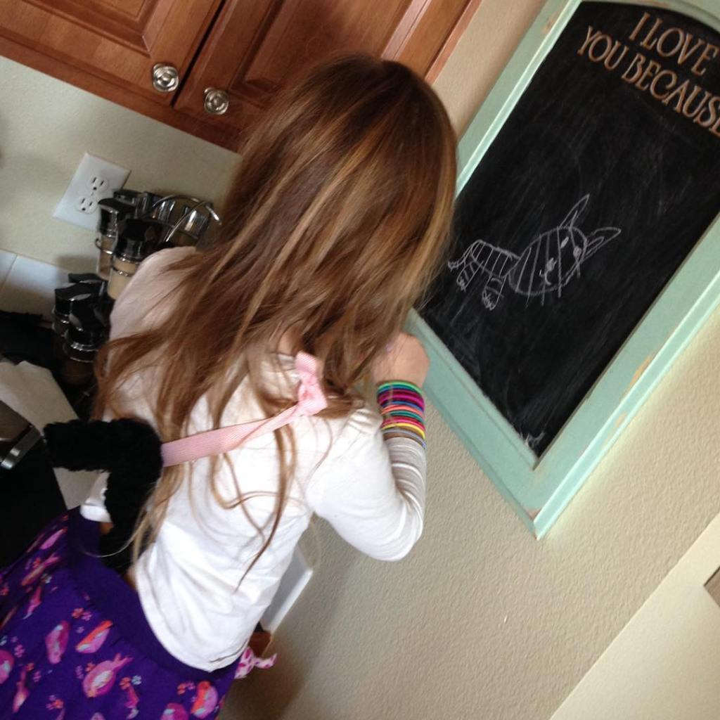 Lyla drawing a cat on the chalk board whilst wearinghellip