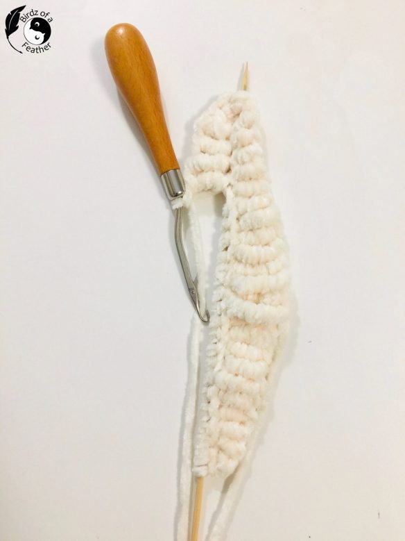crochet coral reef pattern sea pen showing one side complete and latch hook starting on the other side of skewer.