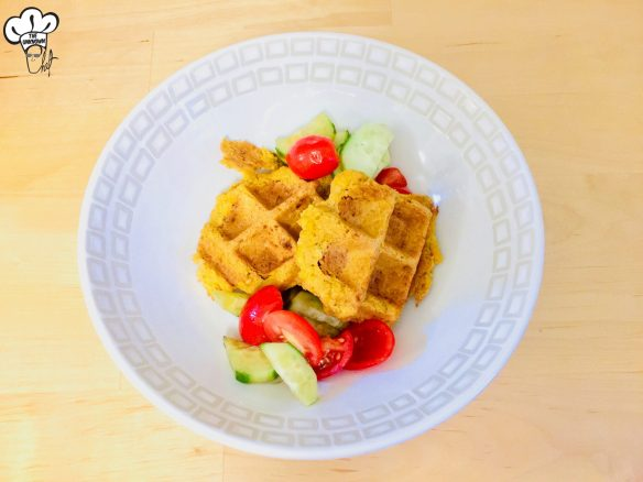 Two falafel waffle in a bowl with tomato salad
