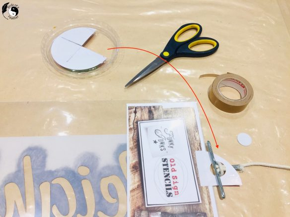 Cutting tabs from plastic lid to hang stencils for how to stencil on wood