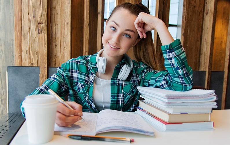 girl at table doing homework looking at camera