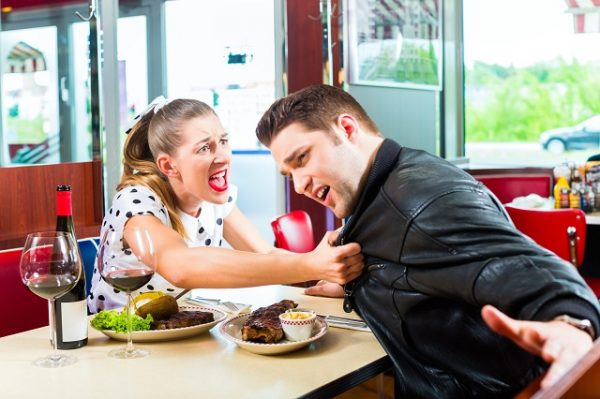 Couple eating and drinking in fast food diner