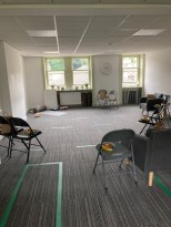 A room set up for teaching, with chairs and mats.