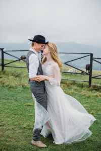 stylish young newlyweds cuddling and smiling in mountainous countryside