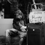 Homeless man with suitcase and sign