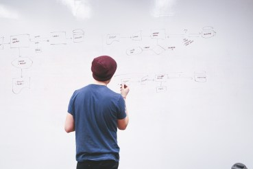 a boy in a hat making a content marketing strategy on a white board
