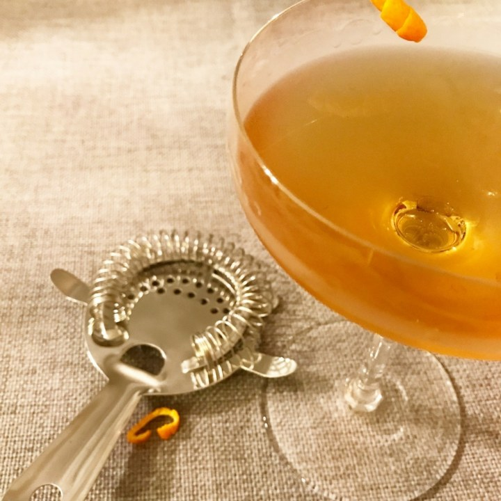 This photo is of a finished Kentucky Flyer Whiskey Cocktail with a twist of orange, sitting next to a stainless steel cocktail strainer.