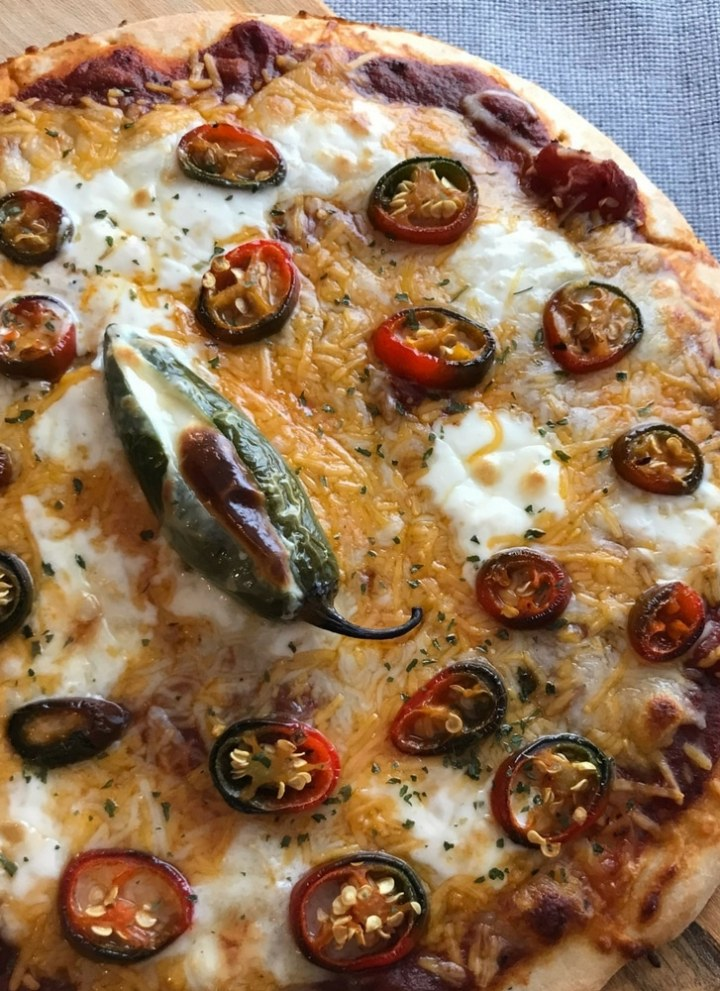 Photo of whole Roasted Jalapeno Popper Pizza Pie on Grey Linen Background Soooo Yummy! This Roasted Jalapeño Popper Pizza is easy to make, CHEESY, and full of pepper flavor! #jalapeño #pizza #vegetarian #homemadepizza #jalapenopopper #jalapeñopopper