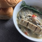 Photo of a close up bowl of vegetarian chicken soup with wild rice in a white bowl. Bread rolls off to the side, and there is a sprig of rosemary on top.