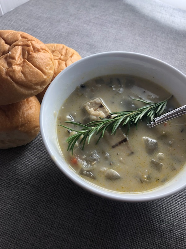 Photo of a bowl of creamy vegetarian chicken soup with wild rice and a vegetarian chicken strip and a sprig of rosemary in a white bowl.  Off to the side are three soft rolls of bread.