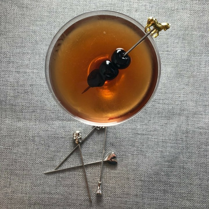 Top down view of Manhattan Cocktail in a coupe glass, garnished with three cherries on a cocktail pick with a gold horse on top.  Other cocktail picks scattered at bottom of glass.