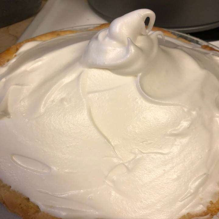 This photo is of a prebaked satsuma meringue pie, piled high with soft white meringue.